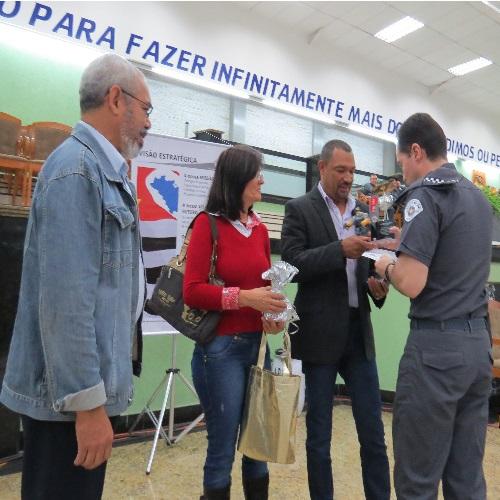 (Foto: Divulgação/APMDFESP)  2º Sgt PM Benedito Miguel, veterano, recebe um presente da APMDFESP, das mãos do Comandante da unidade, Ten. Cel. PM Paulo Cesar da Silva